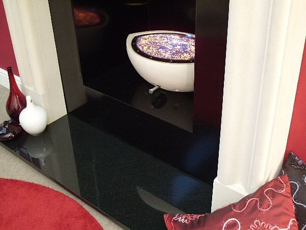 anubis suite with black granite hearth and white firebowl in traditional surround