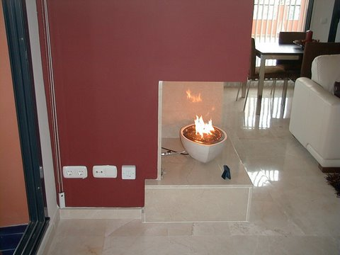 flame detail of white ovla gas fire bowl in corner contemporary fireplace