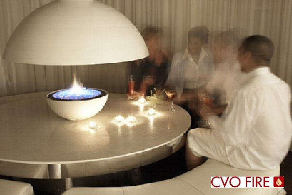circular firebowl cast white stone on table with canopy